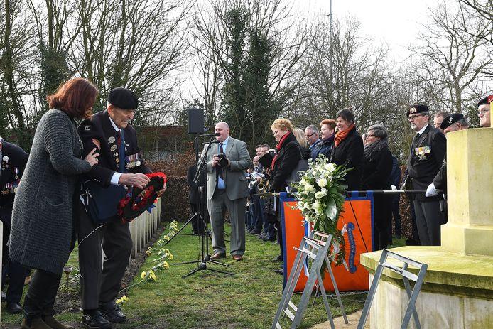 Veteraan Edwin Hunt (99), ondersteund door zijn Nederlandse begeleider van het ministerie van Defensie, legt een krans in Milsbeek.