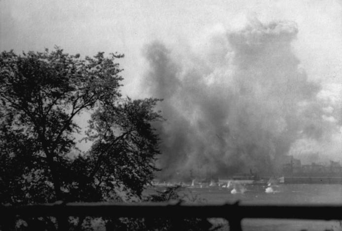 De explosies van de bommen slingeren stukken puin de Maas in tijdens het bombardement.