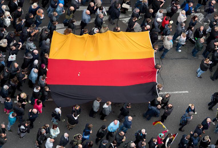 Rechtse betogers van de extreemrechtse partij AfD, de antimoslimbeweging Pegida en Pro Chemnitz dragen de Duitse vlag door de straten.