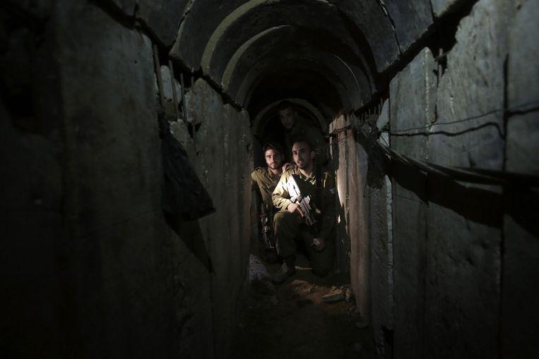 Israëlische soldaten lopen door een tunnel die is ontdekt in het grensgebied. Beeld null