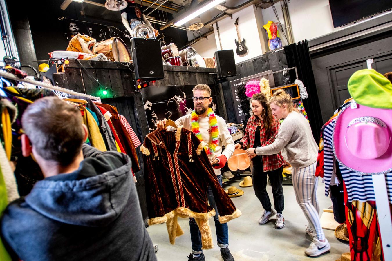 Feestneus Walter (links) was er als de kippen bij om zijn oude kostuum om te ruilen voor iets 'nieuws'. Bas van Hamont (met bril) en zijn collega's helpen een handje.