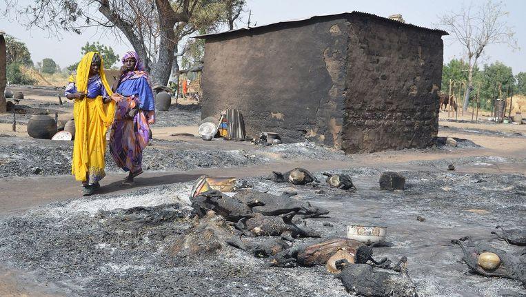 Vrouwen op de vlucht voor Boko Haram passeren een afgebrand dorp. Beeld afp