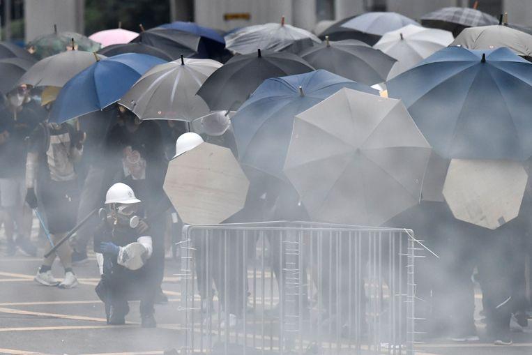 Demonstranten schuilen achter hun paraplu's tijdens als de politie traangas op hen afvuurt.  Beeld AFP