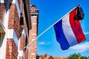 Vlag in de stok met een schooltas erin De officiele examenuitslag volgt op 3 juni, maar examenkandidaten die nu al weten dat ze geslaagd zijn hangen uit vreugde de vlag en hun schooltas al uit het raam.