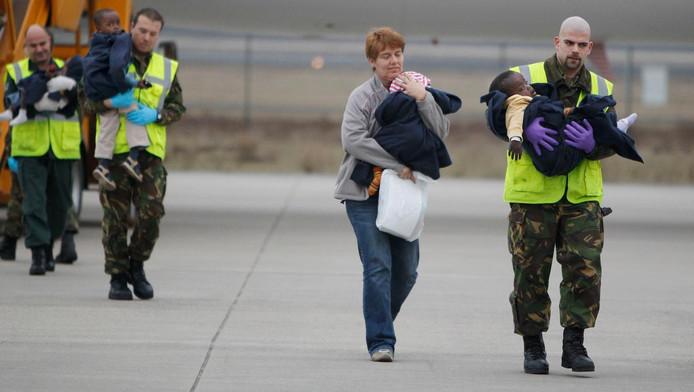 Adoptiekinderen uit Haiti worden na aankomst op vliegbasis Eindhoven door hulpverleners weggeleid van het vliegtuig. 92 kinderen werden opgevangen door Nederlandse adoptieouders in een terminal van de luchthaven.