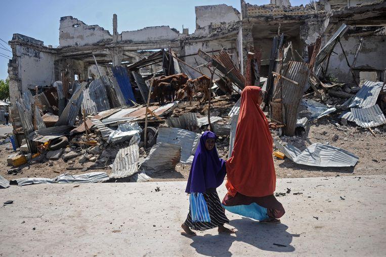 Een vrouw en een kind lopen langs ruïnes die veroorzaakt zijn door een autobom in de Somalische hoofdstad Mogadishu. Archiefbeeld.