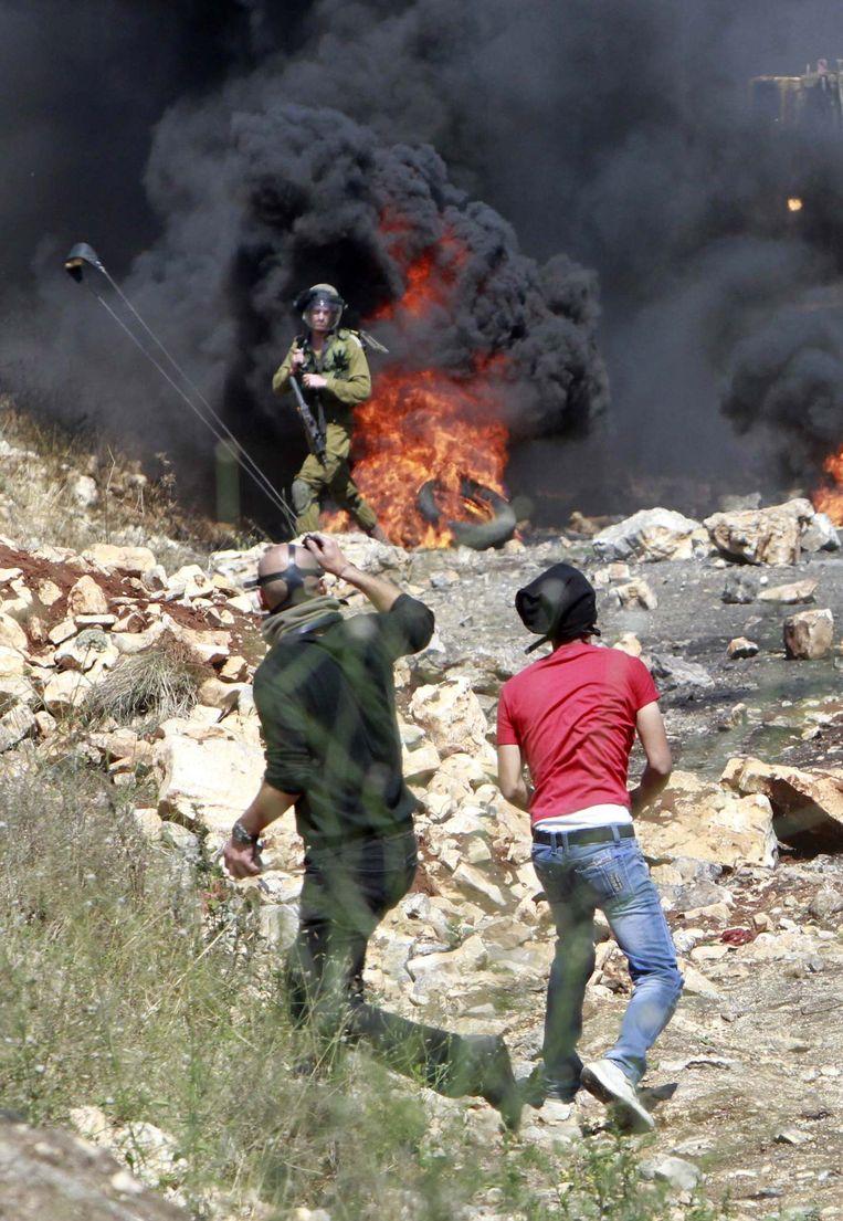 Palestijnse demonstranten gooien stenen naar Israëlische soldaten. Beeld reuters