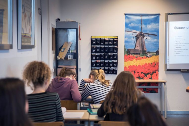 Aan de muur van dit klaslokaal in Culemborg hangt een speciale opbergzak voor de mobiele telefoons. Beeld Werry Crone