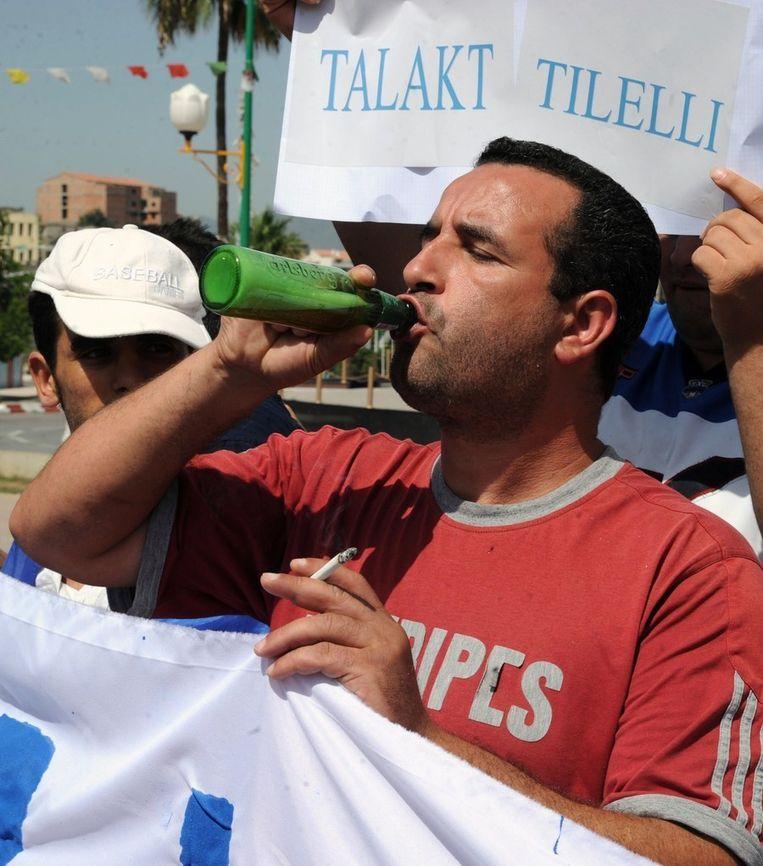 Een Algerijnse demonstrant nuttigt een biertje uit protest.
