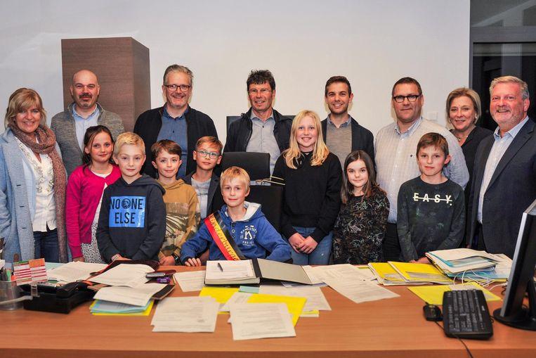 De nieuwe Kindergemeenteraad, met 'burgemeester' Jonas De Souter aan 'zijn' bureau, bijgestaan door het echte schepencollege.