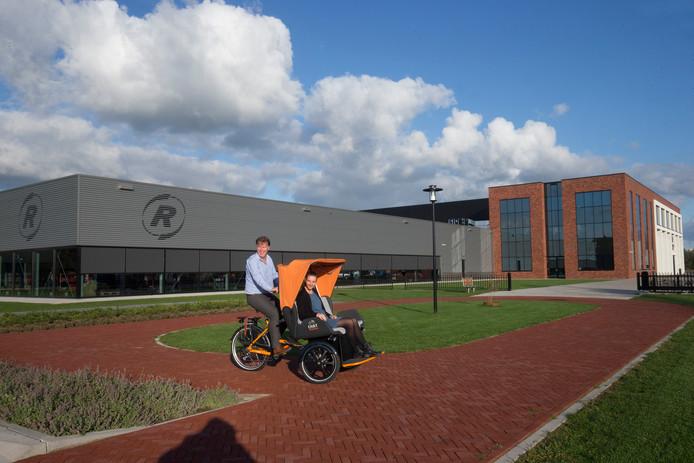 Marnix Kwant en Inge Kluivers in een aangepaste fiets voor het nieuwe bedrijfspand.