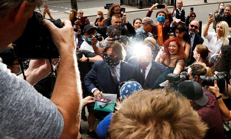 Johnny Depp begroet zijn fans voordat hij vrijdag in Londen voor de rechter verschijnt.  Beeld John Sibley / Reuters