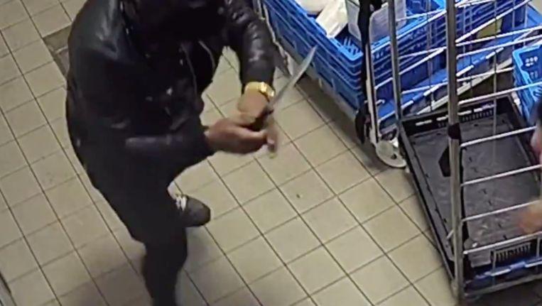 Een van de verdachten bedreigt een medewerker met een groot mes. Beeld Politie Amsterdam