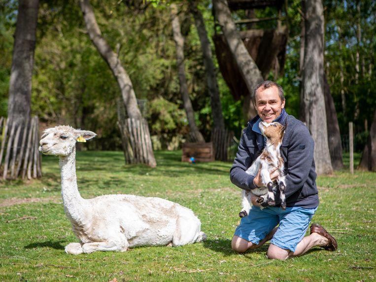 Sam Rutherford met één van de alpaca's en een geitje in zijn tuin in Sint-Genesius-Rode die hij openstelt voor iedereen.
