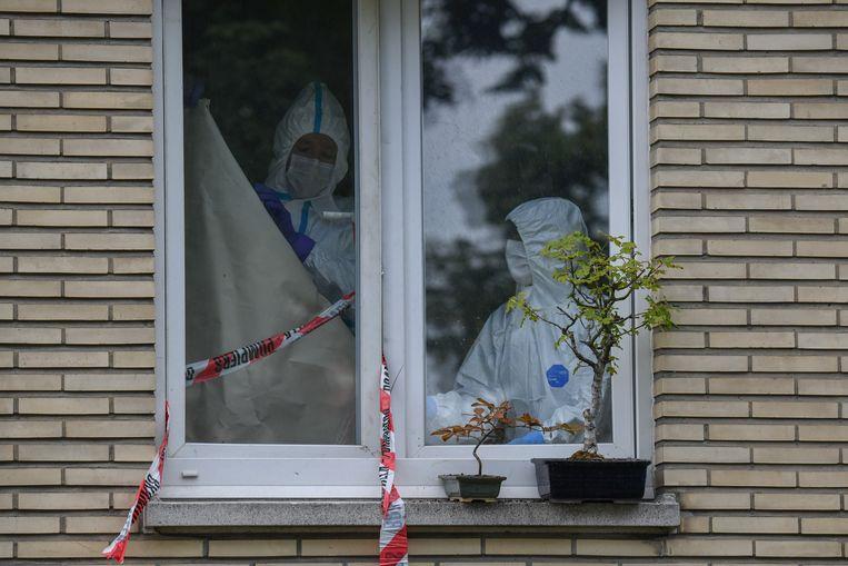 Medewerkers van het labo onderzoeken de flat in Berchem waar agenten de lichamen van vader en zoon vonden.