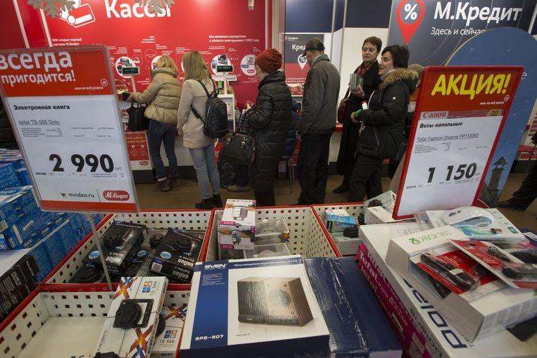Veel Russen stonden de afgelopen dagen in de rij om nog allerlei importproducten te kopen, om prijsstijgingen door de val van de roebel voor te zijn. Beeld ap