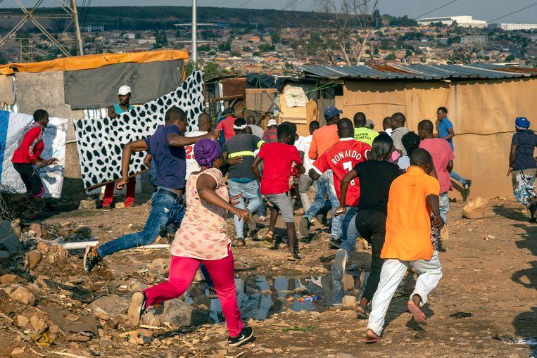 Protesterende bewoners van een township in Johannesburg slaan op de vlucht voor soldaten.  Beeld AP