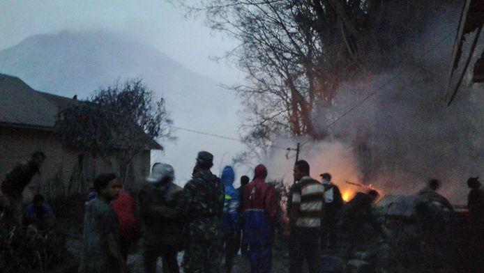 Bewoners en reddingswerkers bij een brandende boom nadat deze geraakt werd door de uitbarsting van de vulkaan Sinabung.
