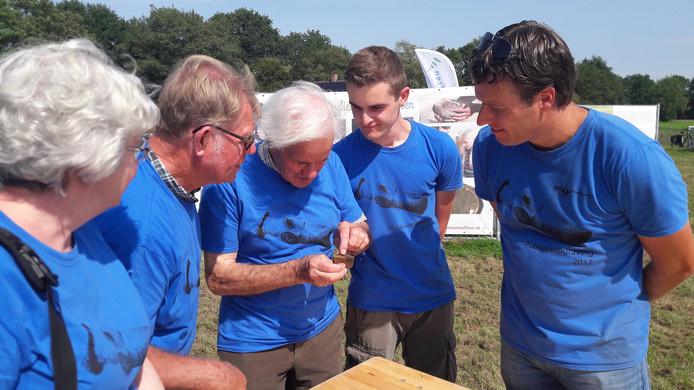 Archeoloog Niels Bouma (rechts) toont een vondst aan leden van de Historische Kring Dalfsen, die sinds kort een werkgroep Archeologie heeft.