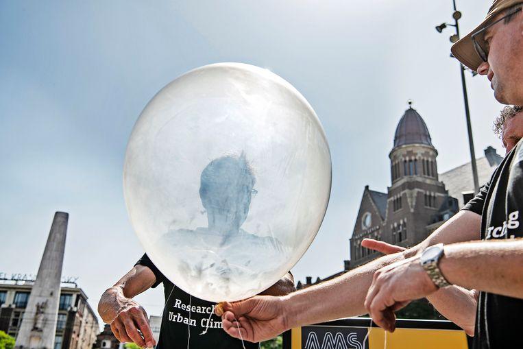 Het AMS, instituut voor Advanced Metropolitan Solutions, laat een weerballon op de Dam om de hitte te meten . Beeld Guus Dubbelman / de Volkskrant