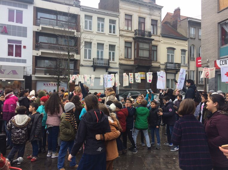 Leerlingen hangen vlagjes en tekeningen op aan Zwarte Vijvers. Ze willen vooral een positieve boodschap verspreiden over Molenbeek.