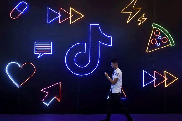 Een man loopt met zijn smartphone in de hand langs het logo van Tiktok.