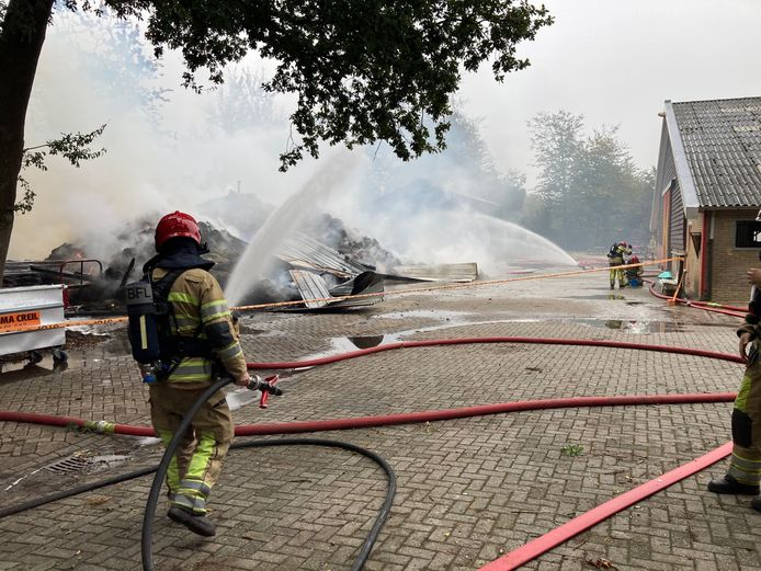 Brandweer mannen blussen na, bij de grote schuurbrand op een manege in Emmeloord.