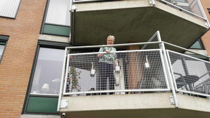 Anna Hartman (86) van De Posten wordt met touw en tas via het balkon voorzien van wat spulletjes. Ze helpt haar familie haar de komende tijd.