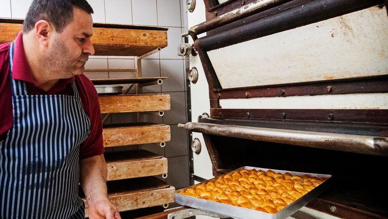 Een Rotterdamse bakker in een Turkse bakkerij bereidt baklava en ander banket. Baklava wordt veel gegeten tijdens het Suikerfeest aan het einde van de ramadan, de islamitische vastenmaand. Beeld anp