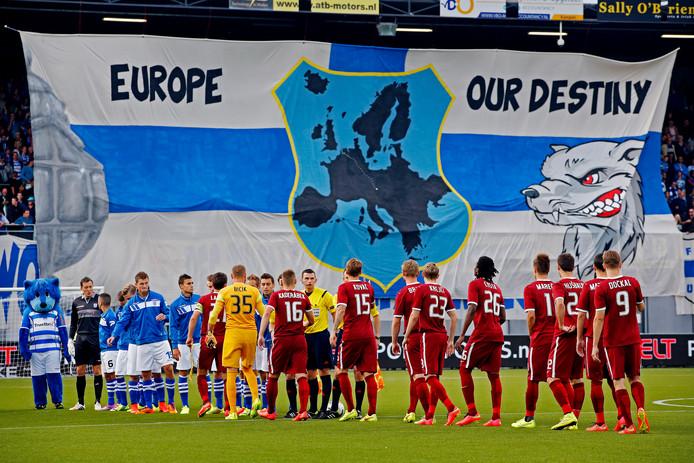 De spelers van Sparta Praag en PEC Zwolle schudden elkaar de hand. De harde kern van PEC Zwolle pakte flink uit met een groot spandoek.