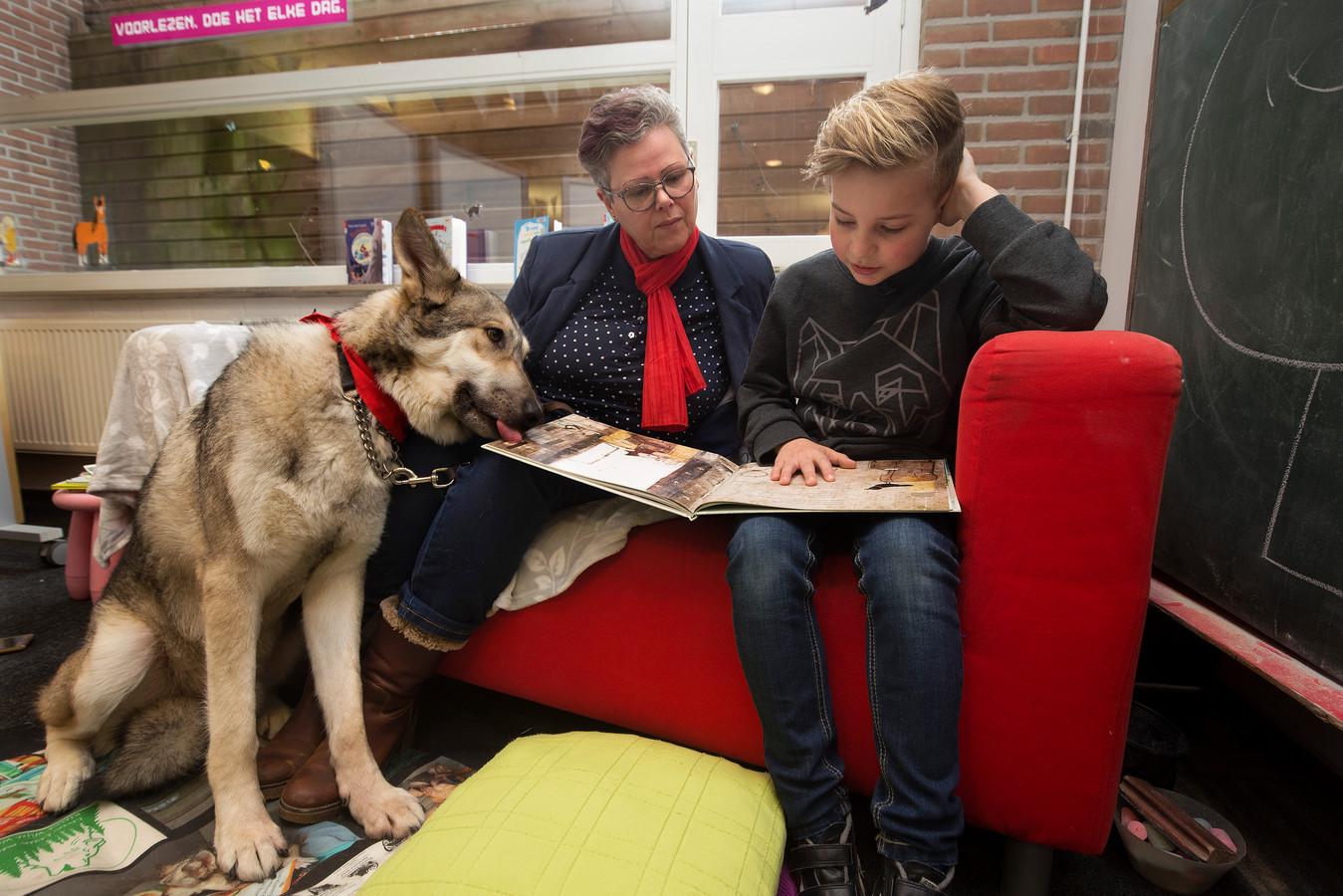 Floris Hulzink (9) mag als eerste voorlezen aan een speciaal daarvoor opgeleide hond in de bibliotheek in Aalten.
