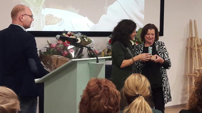 Mieke van der Loop ontvangt de Tilburg Trofee uit handen van locoburgemeester Hendrickx.