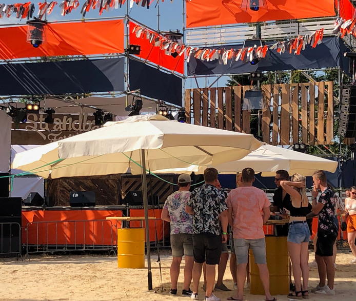Lekker onder de parasol op het Strandbalfestival in Bornerbroek.