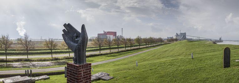 Op de dijk bij Delfzijl de begraafplaats met monument van het voormaligedorpje Oterdum Op de achtergrond o.a.Aldel (rechts) en biocentrale van Eneco (rood). Beeld Harry Cock