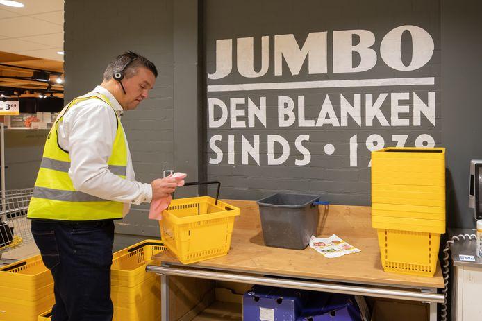 Manager Floor van den Berg maakt winkelmandjes schoon bij de Jumbo in Baarn.