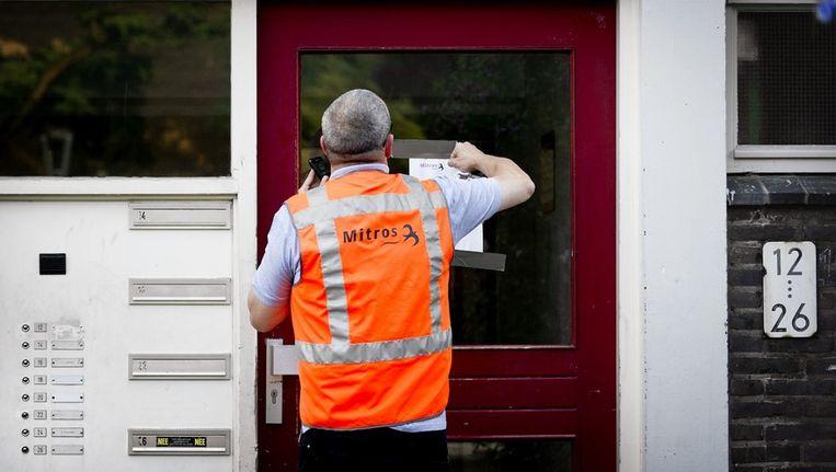 Een medewerker van woningbouwvereniging Mitros verwijdert een asbest waarschuwing. Beeld anp