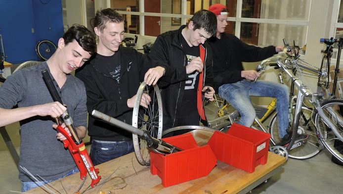 Eric Blom, Marcel van Beckhoven en Kaylian Vermeer leren hoe ze een fietswiel moeten spaken.