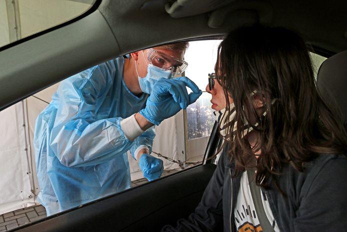 Een student laat zich in de drive-in testlocatie van de GGD aan de A12 bij Nootdorp testen op het coronavirus.