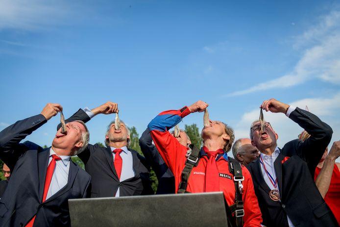 Het Twents Haringcomité laat een Hollandse Nieuwe langs de huig glijden.