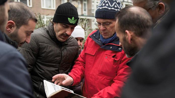 Paul Groenendijk van Platform Wederopbouw Rotterdam geeft de vluchtelingen een rondleiding door het centrum.