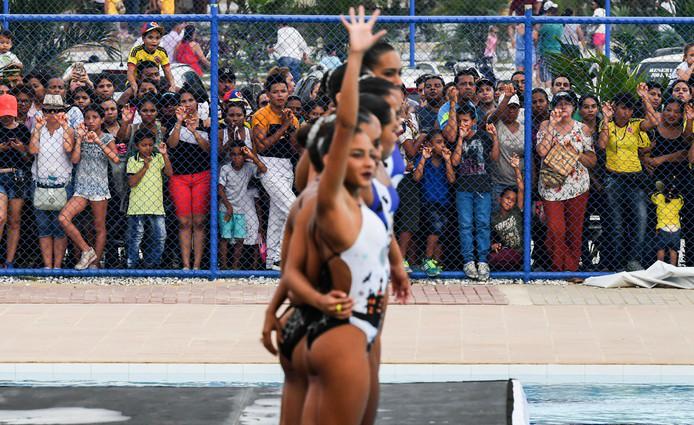 Colombianen kijken voor het hek van het zwembad naar het team van Chili tijdens een wedstrijd synchroonzwemmen in Santa Marta. Foto Luis Acosta