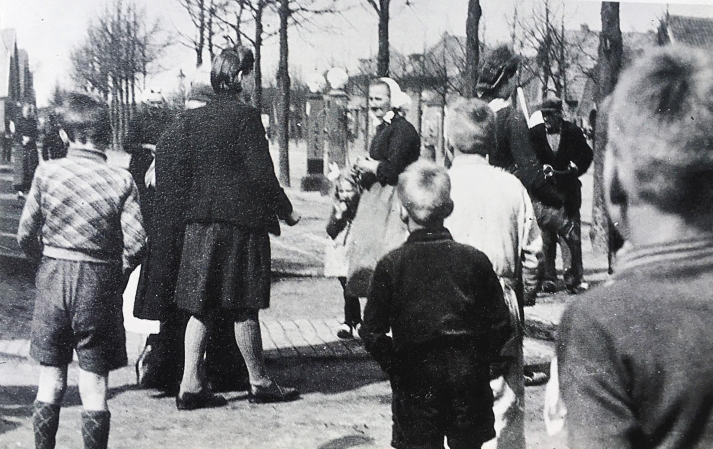 Zo ogenschijnlijk gewoon begon de reis die in het vernietigingskamp Sobibór zou eindigen: Izaäk Heijman (half zichtbaar achter zijn dochter Rachel) wordt naar de bus begeleid, die hem naarWesterbork brengt.