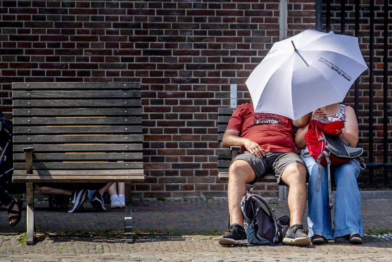 Een stel zoekt de schaduw op onder een paraplu. Beeld EPA