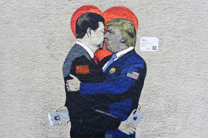 Komt er een einde aan de smartphone-oorlog tussen China en de VS? Een Italiaanse straatartiest loopt er met zijn muurschildering in Milaan al op vooruit.