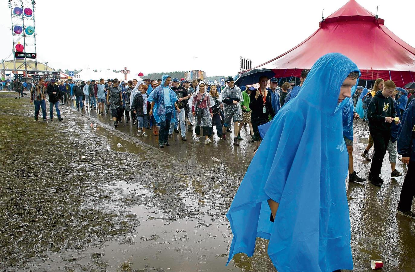 Bezoekers van Lowlands lopen in de regen tijdens de editie van 2002.