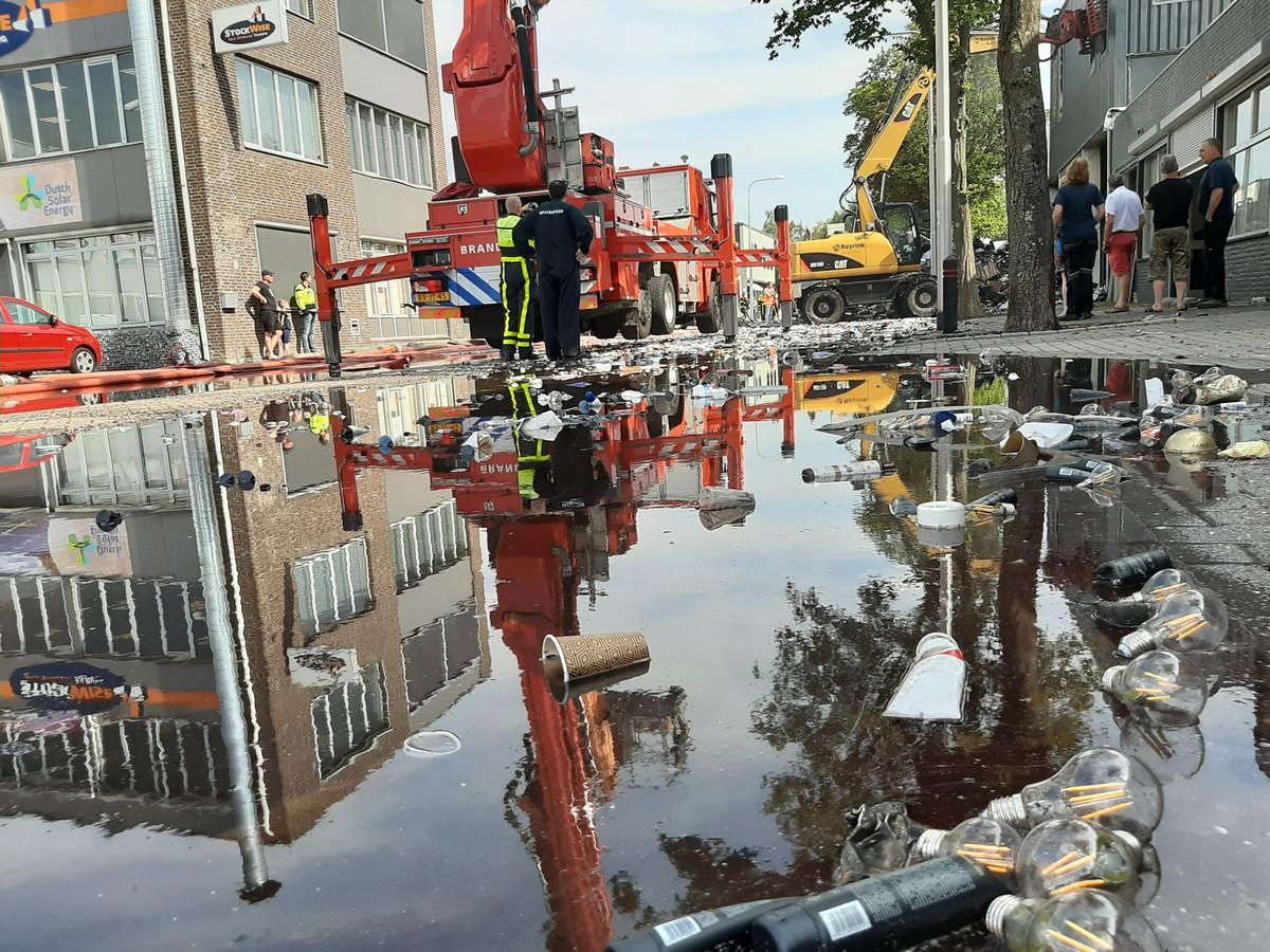 Lampen en cosmeticaproducten stromen met het bluswater weg tijdens het nablussen van de brand in de Kapitein Rondairestraat in Tilburg.