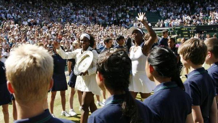 Serena Williams(L) en haar zus Venus na de partij (AFP) Beeld