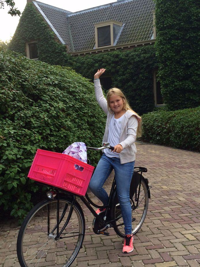 Prinses Amalia zwaait in augustus 2015 als ze op de fiets vanaf Villa Eikenhorst in Wassenaar voor het eerst vertrekt naar haar nieuwe middelbare school, het Christelijk Gymnasium Sorghvliet in Den Haag. De foto is gemaakt door koning Willem-Alexander.