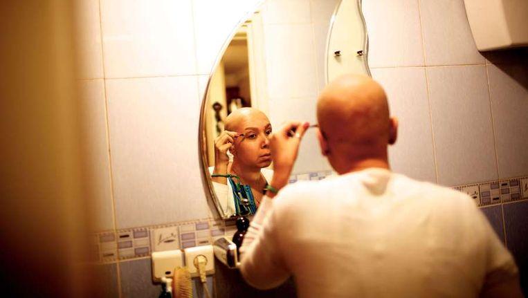 Een Iraanse borstkankerpatiënt in de badkamer van haar ouders huis in Teheran. Beeld afp