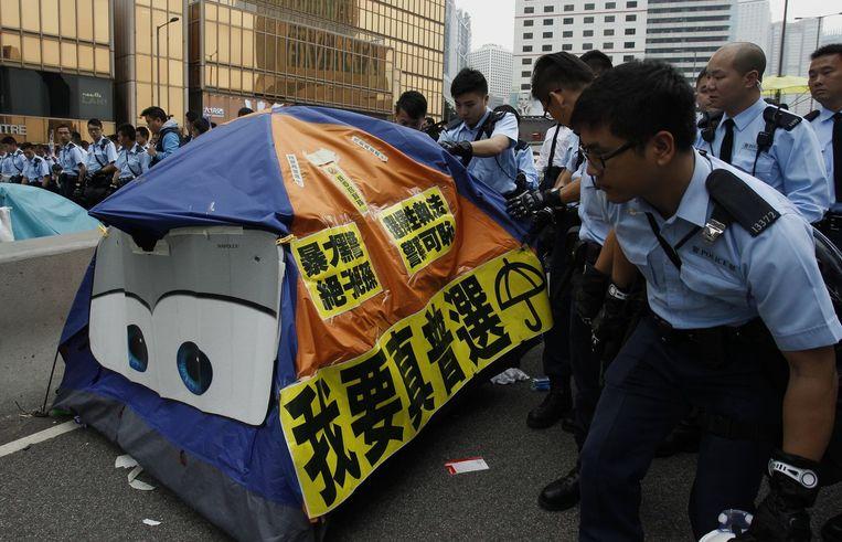 Politieagenten kijken of er demonstranten in de tent zitten. Beeld reuters